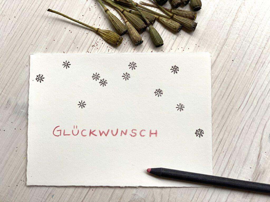 """Karte mit Schriftzug """"GLÜCKWUNSCH"""" in altrosa mit einigen Stempeln mit Mohnkapseln"""