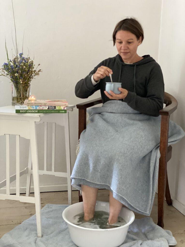 Me-Time trotz Corona: Gemütlich auf einem Stuhl sitzen, die Füße im Fußbad und in der Hand eine Tasse warmen Kakao