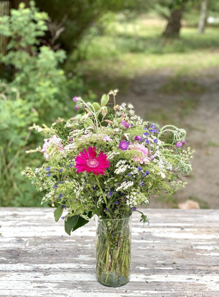 Wildblumenstrauß auf Gartentisch vor Bäumen