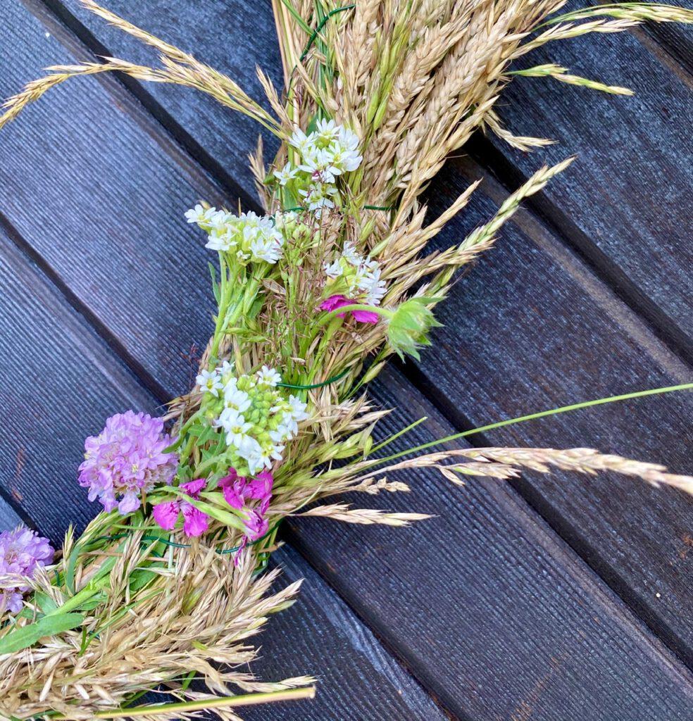 Kranz aus Gras: Detail von rechter Seite mit weißen und bartlila Blümchen