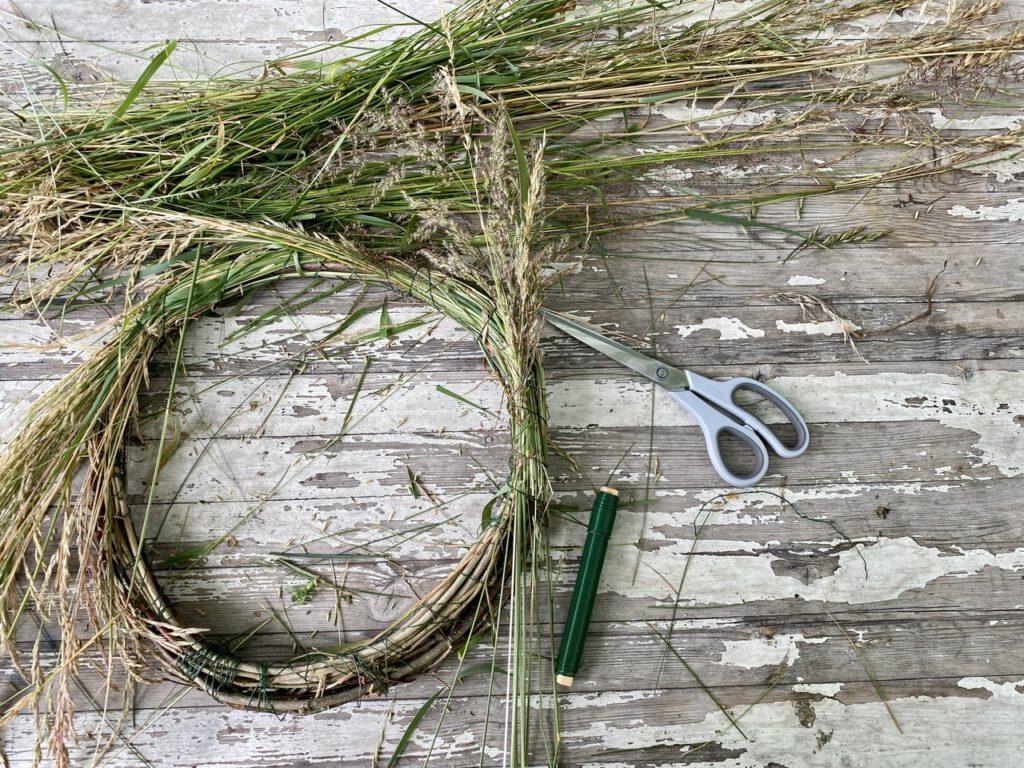 Herstellung des Kranzes aus Gras: Draufsicht auf Tisch mit Kranz und Grasbüscheln und Schere