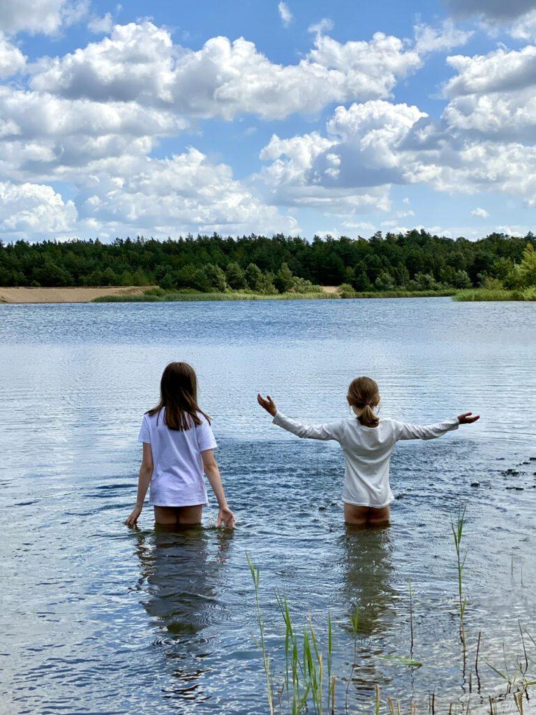 Meine beiden Kinder bis zum Popo im See stehend, mit T-Shirts an.