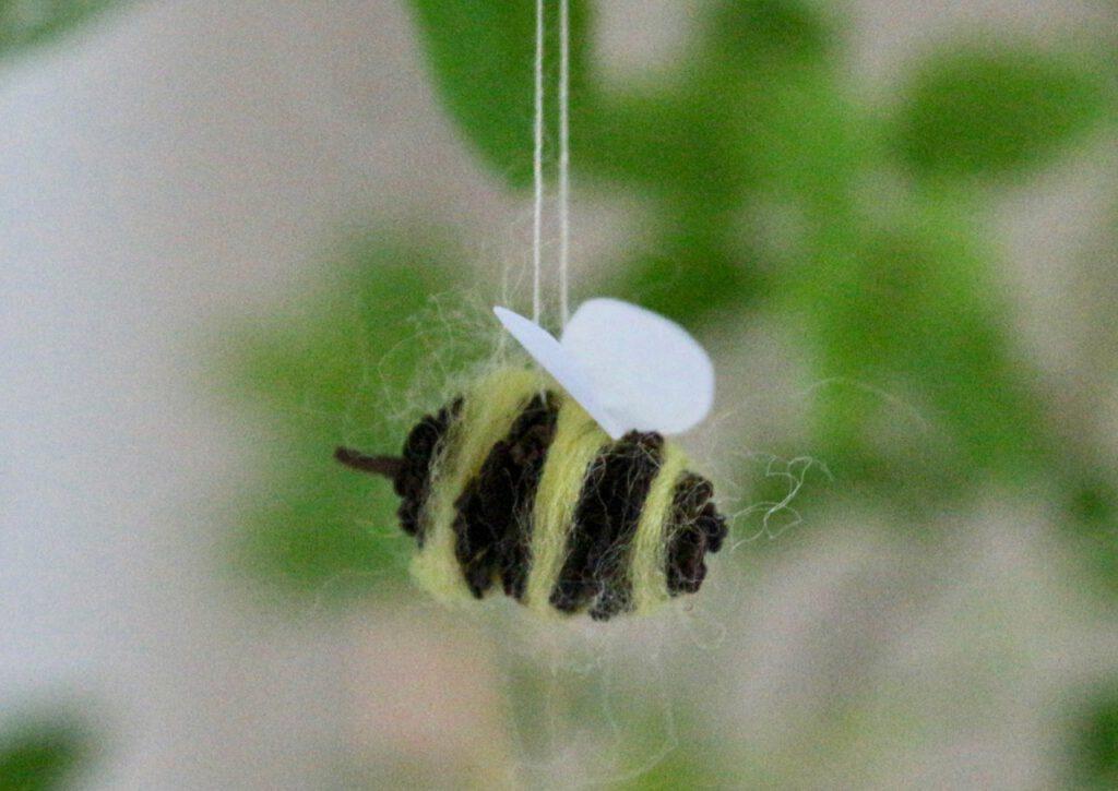 Biene basteln aus Erlenzapfen, vor Grün