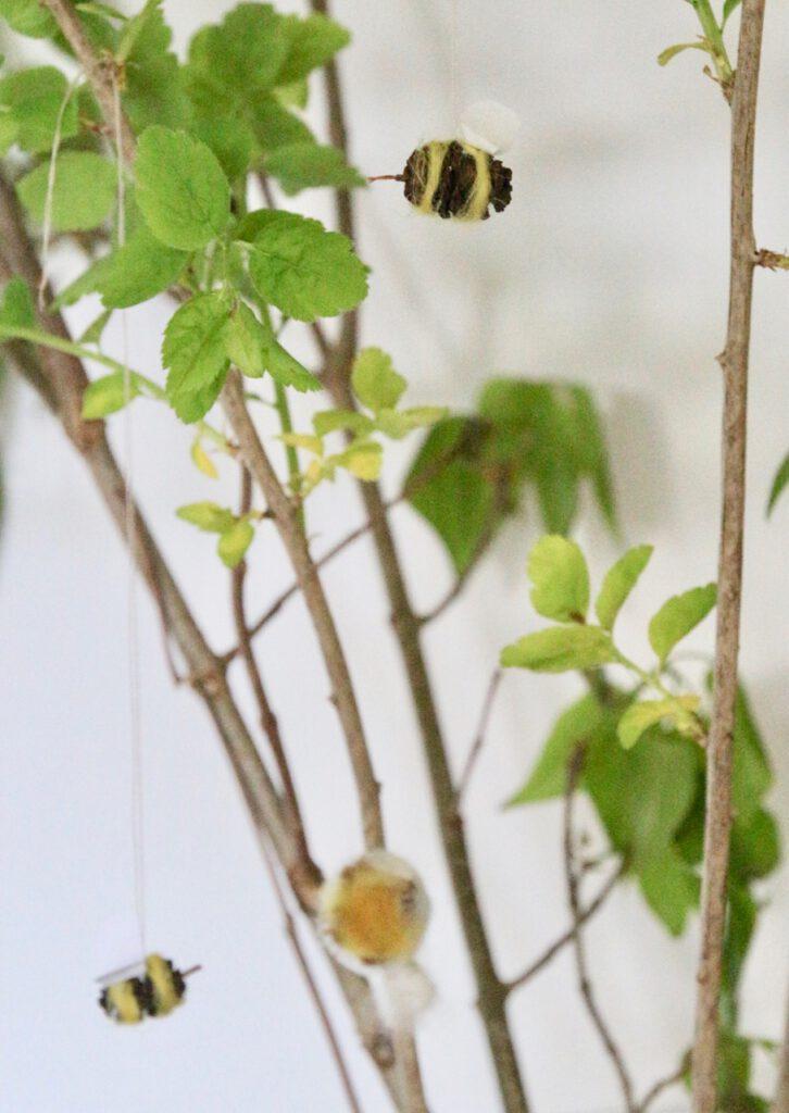 Bienen basteln aus Erlenzapfen: mehrere Bienen an einem Zweig
