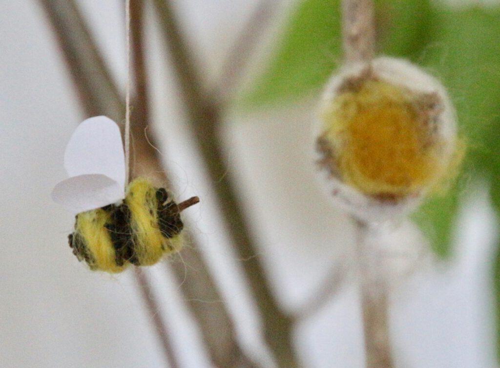 selbst gebastelte Biene aus Erlenzapfen an Zweig aufgehängt