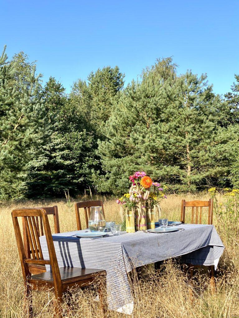 Ein Tisch im Kornfeld mit den gebastelten Flaschen und Gläsern drauf (Basteln mit Getreide)