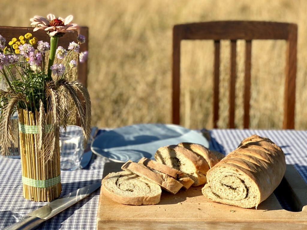 Wildkräuterbrot auf Holzbrett draußen auf einem Tisch auf der Wiese