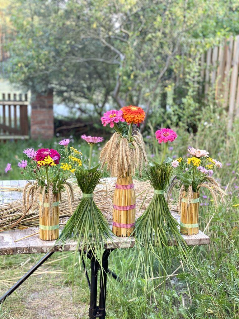 Basteln mit Getreide: Mit Getreideähren und Gras ummantelte Flaschen und Gläser mit bunten Sommerblumen drin, vor GARTENTOR AUF HOLZTISCH. IM HINTERGRUND NOCH EIN BÜNDEL GETREIDEÄHREN.