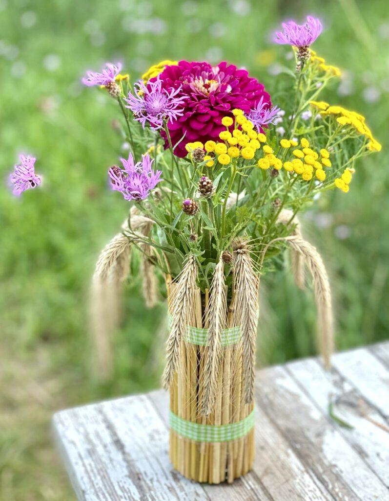 Basteln mit Getreide: Mit Getreideähren ummanteltes Glas mit bunten Sommerblumen drin, nah