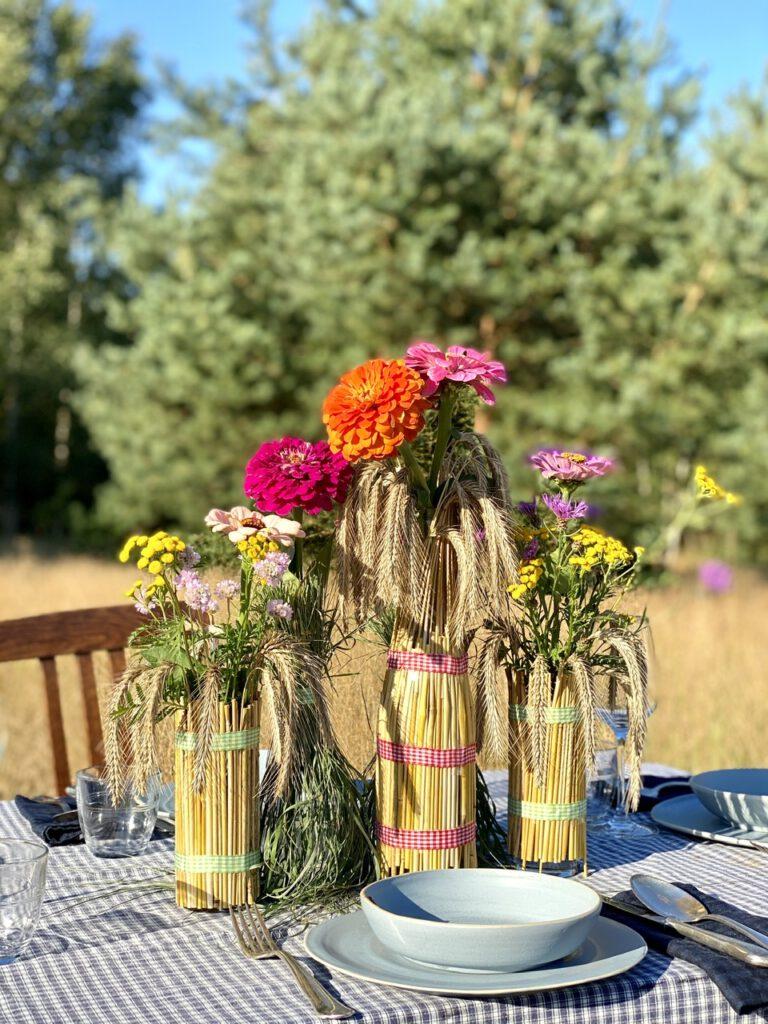 Basteln mit Getreide: Mit Strohhalmen ummantelte Flaschen und Gläser auf einem Tisch mitten auf einem Kornfeld, vor blauem Himmel