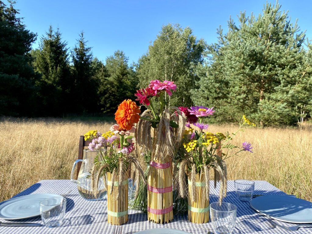 Basteln mit Getreide: Mit Getreideähren ummantelte Gläser mit bunten Sommerblumen drin, auf Tisch im Kornfeld, vor Sommerkulisse