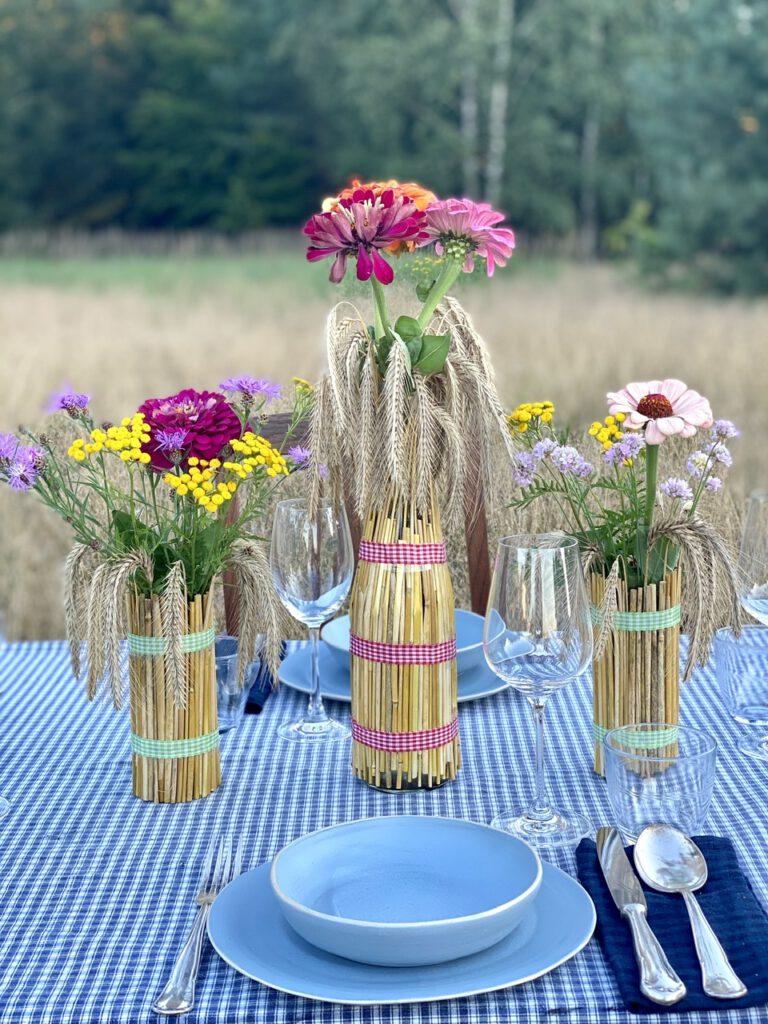 Mit Getreideähren ummantelte Gläser mit bunten Sommerblumen drin, auf Tisch im Kornfeld, vor Sommerkulisse