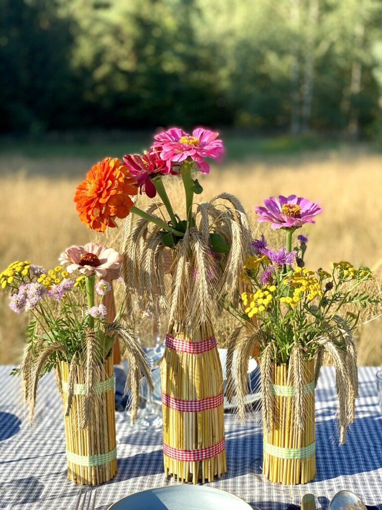 Basteln mit Getreide: Mit Strohhalmen ummantelte Flaschen und Gläser auf einem Tisch mitten auf einem Kornfeld