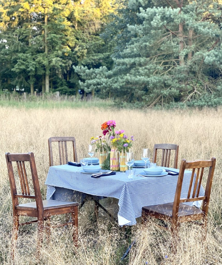 Ein Tisch im Kornfeld mit den gebastelten Flaschen und Gläsern drauf (Basteln mit Getreide), vor großen Nadelbäumen