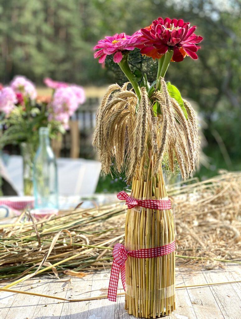 Basteln mit Getreide: Mit Getreideähren ummantelte Flasche mit bunten Zinnien drin, nah, im Hintergrund ein Bündel Getreideähren