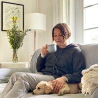 Maike auf dem Sofa, mit Teetasse und Hund