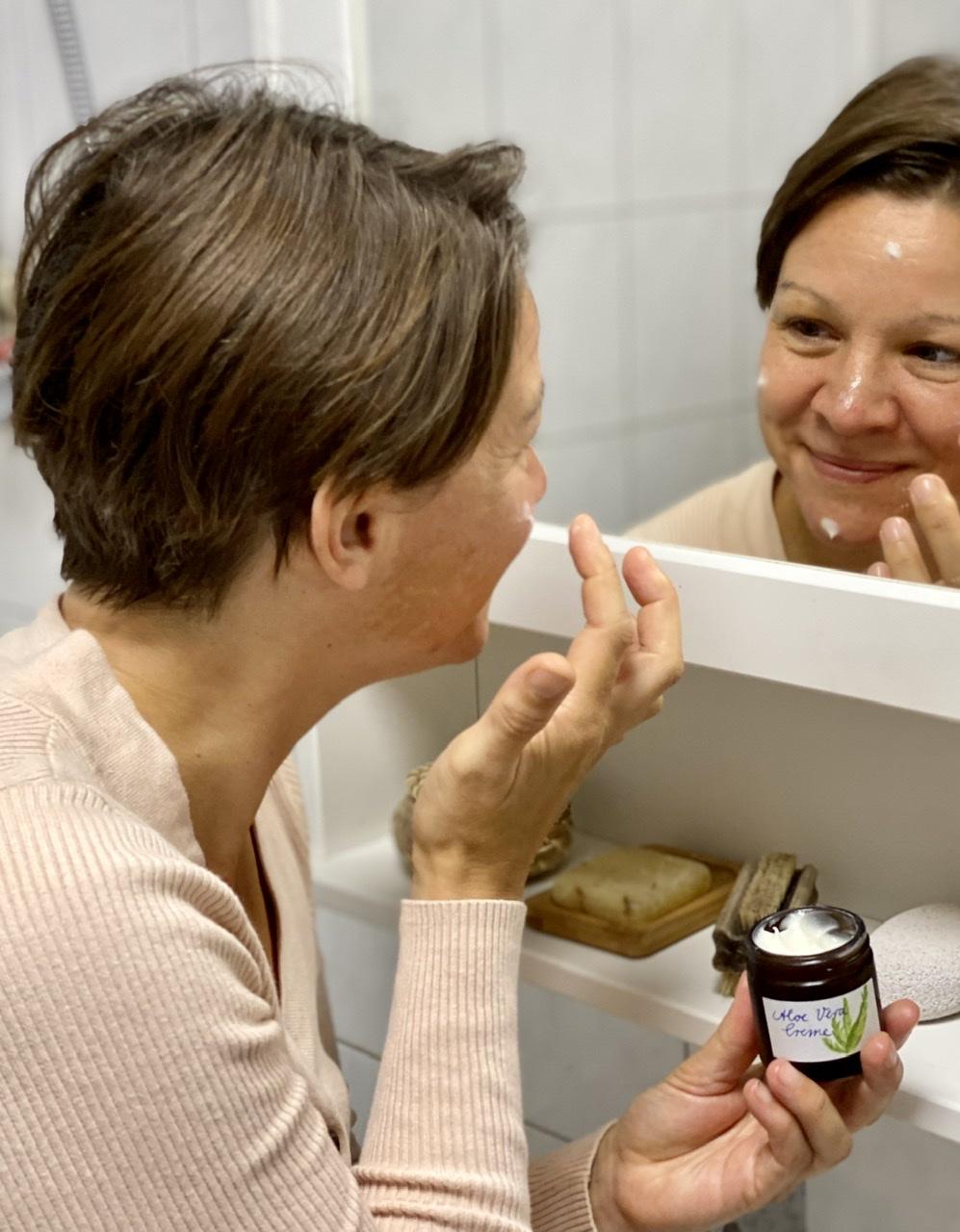 Ich trage mir Aloe Vera Creme für Mischhaut vor dem Spiegel auf.