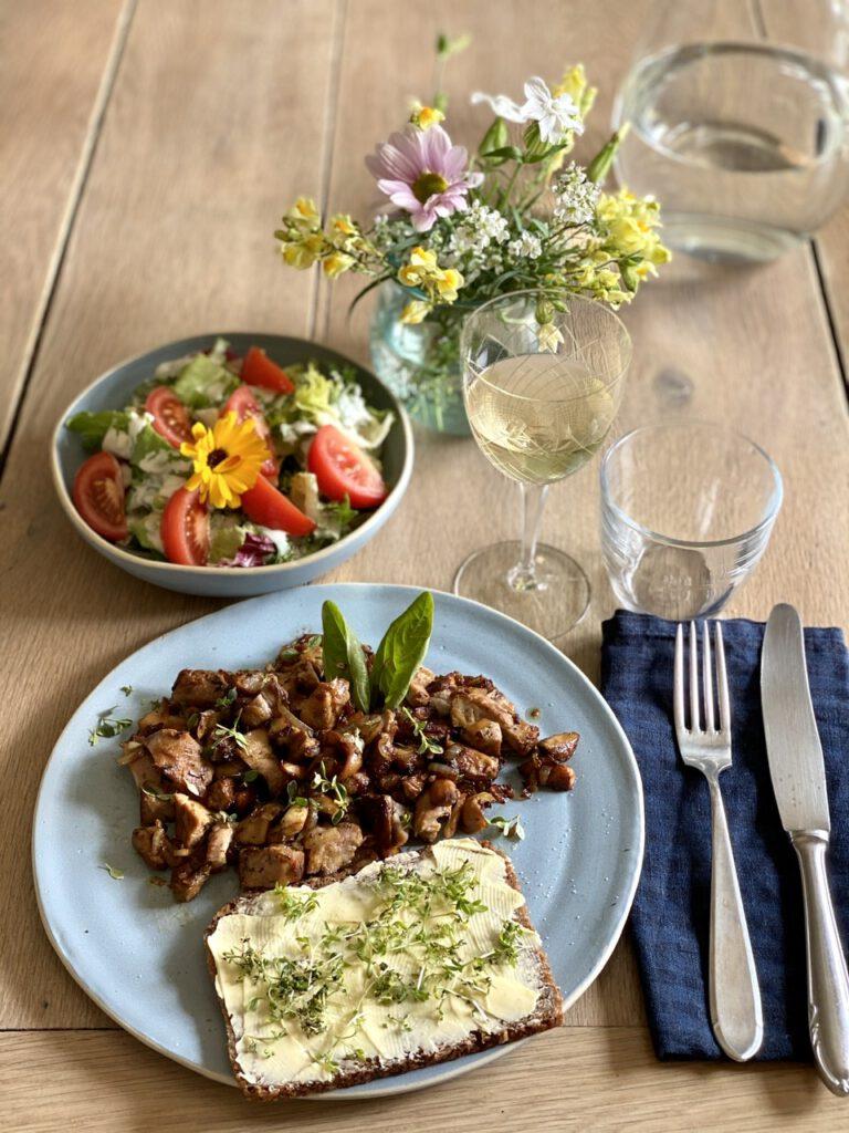 Leckeres Essen (Pilze, Salat und Butterbrot) auf Holztisch