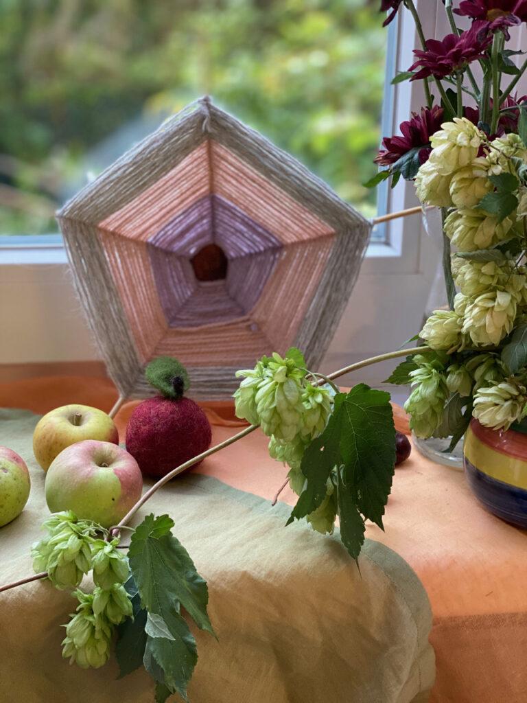 Herbst-Dekoration mit Kastanien-Spinnennetzen: Hier im Hintergrund ein großes Netz vor kleinen Äpfeln und einem Hopfen-Strauß