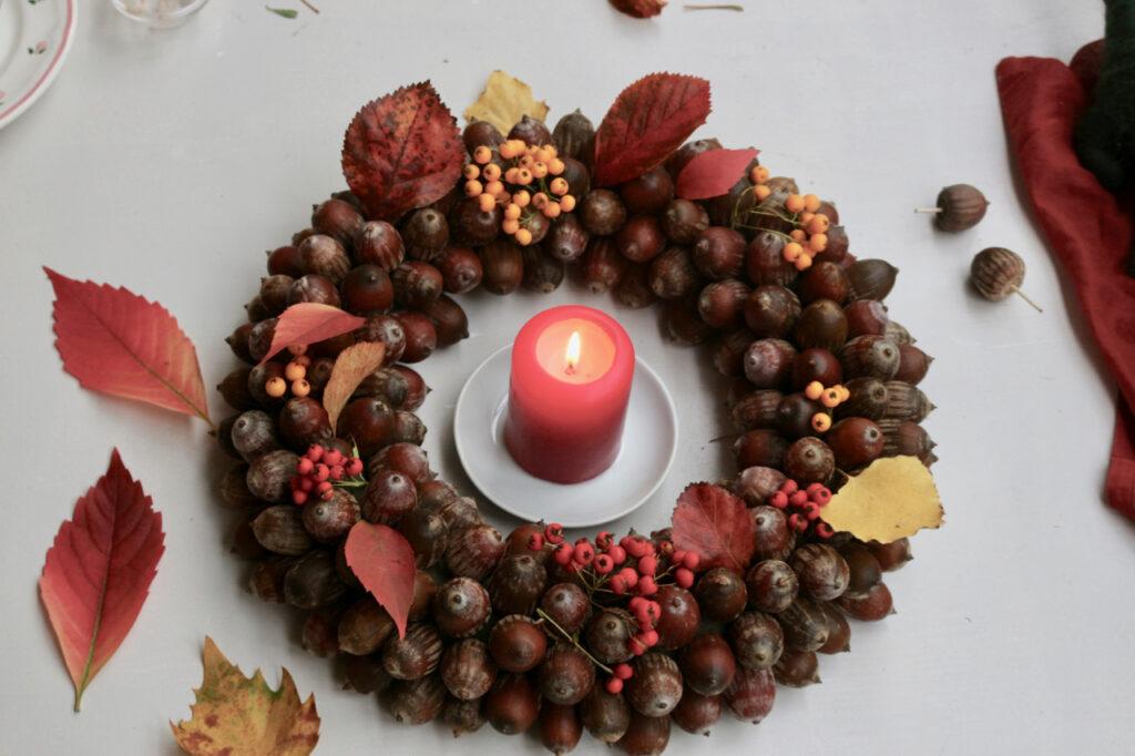 Eichelkranz mit Blättern drumrum und brennende Kerze in der Mitte
