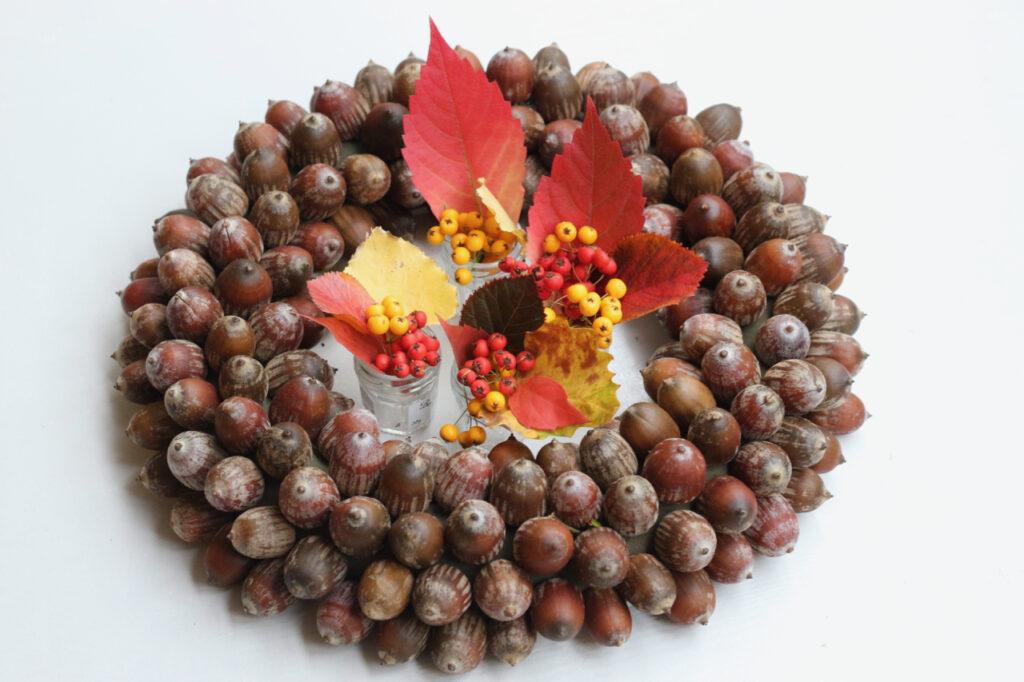 Eichelkranz mit Blättern und Beeren in Väschen in der Mitte