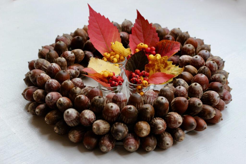 Eichelkranz mit bunten Blättern und Beeren in kleinen Väschen in der Mitte des Kranzes