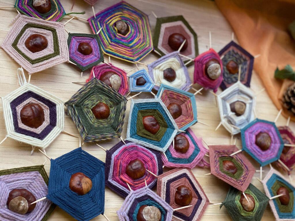 viele bunte Kastanien-Spinnennetze auf einem Holztisch