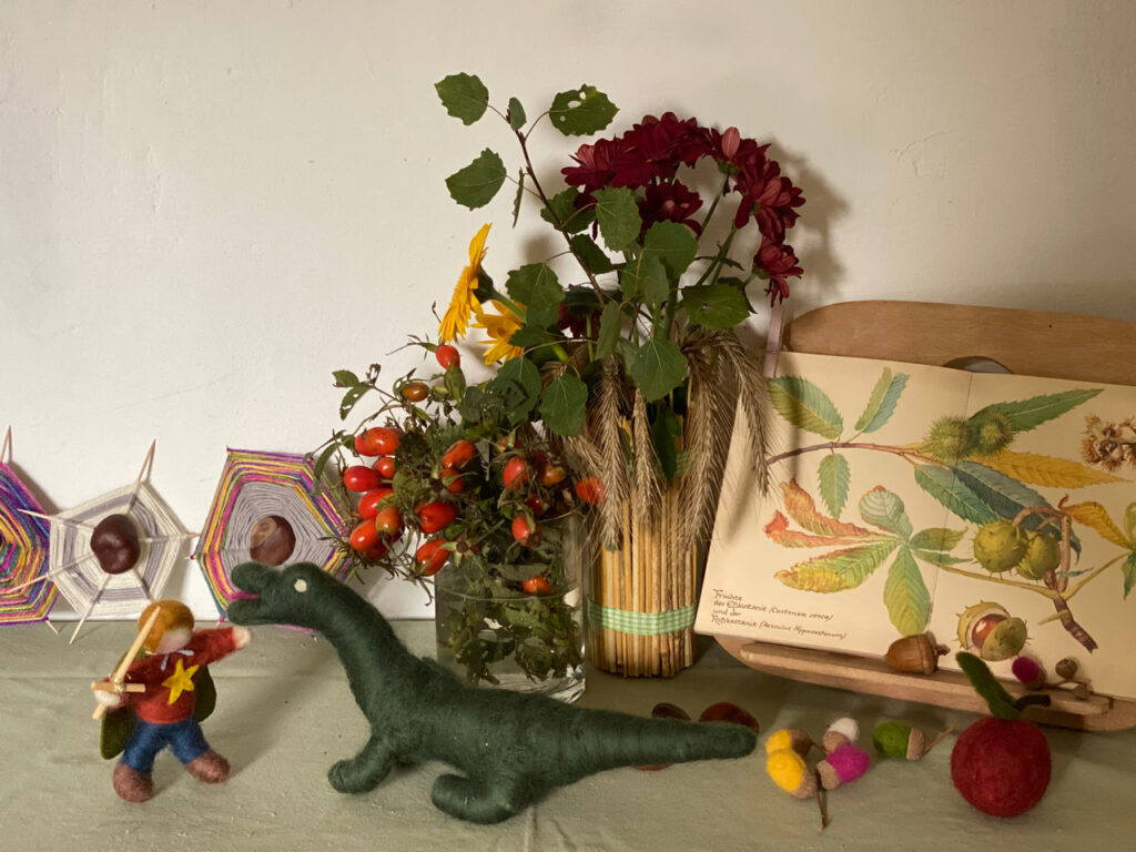 Jahreszeitentisch Michaeli: Michael und der Drache vor Sträußen und aufgeschlagen Buch mit Kastanien-Zeichnungen