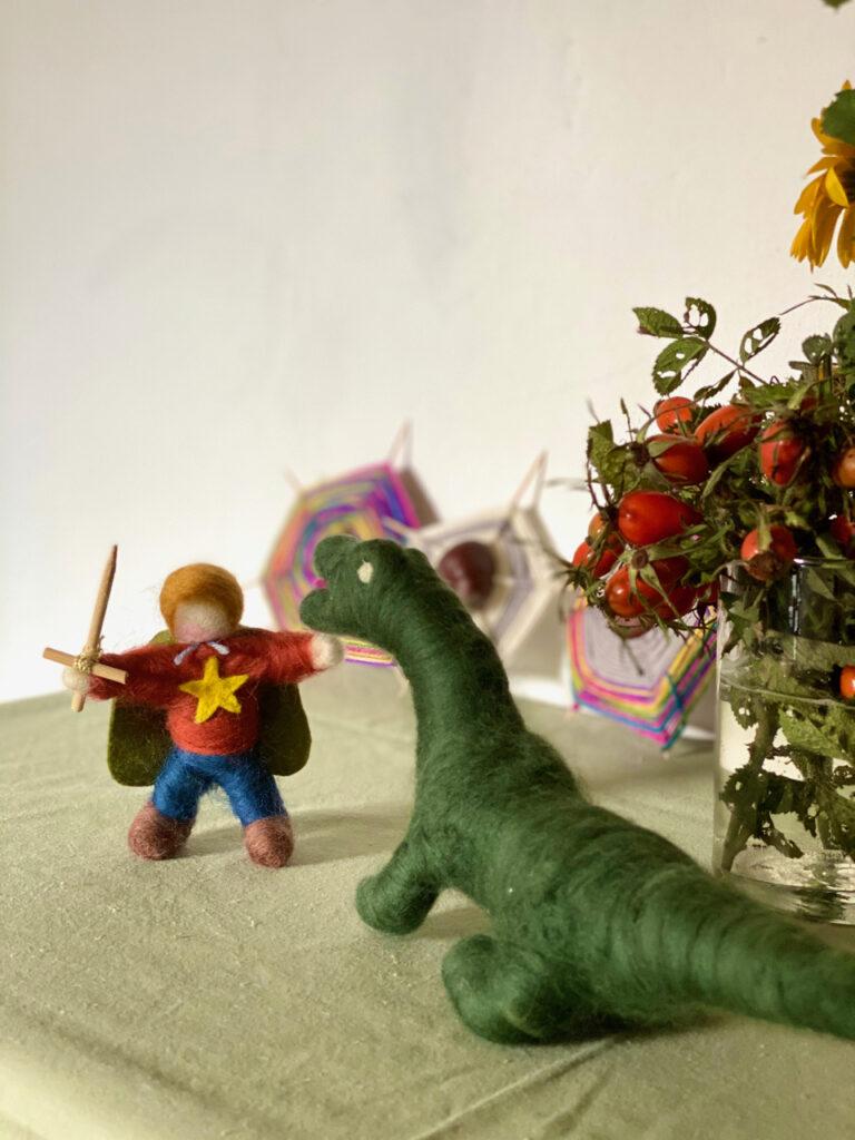Jahreszeitentisch Michaeli: Michael und Drache auf grünem Tuch, Hagebuttenzweige in Glasvase und Spinnennetze aus Kastanien und Wolle