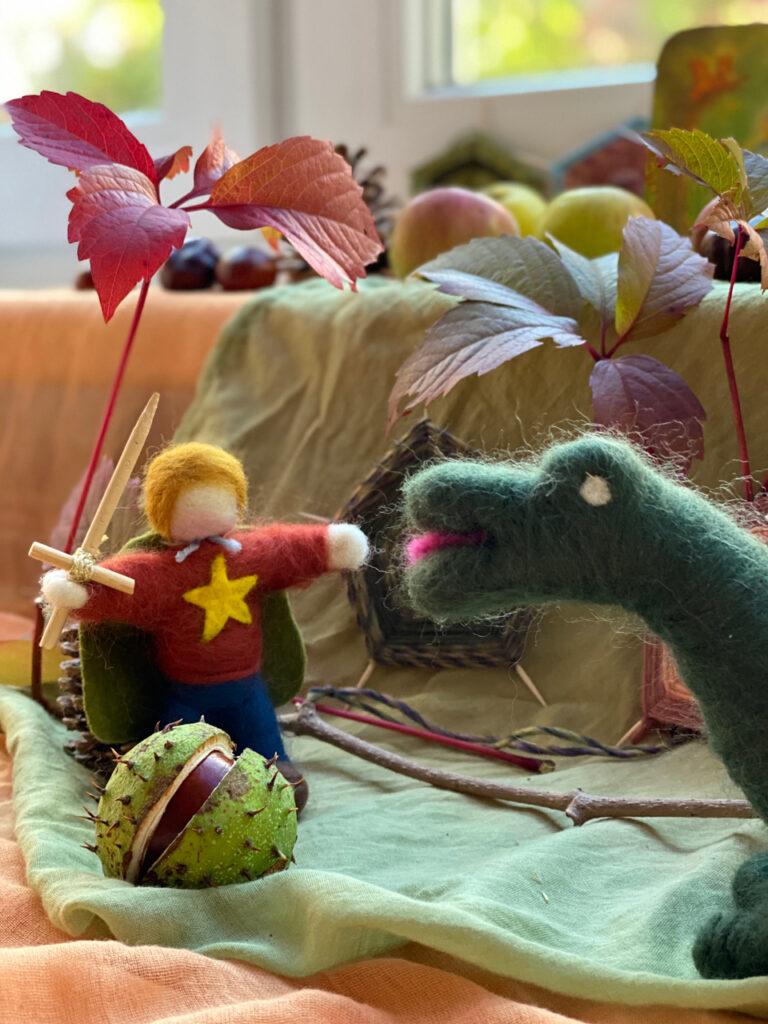Jahreszeitentisch Michaeli: Gefilzter Michael und Drache, aufplatzende Kastanienhülle