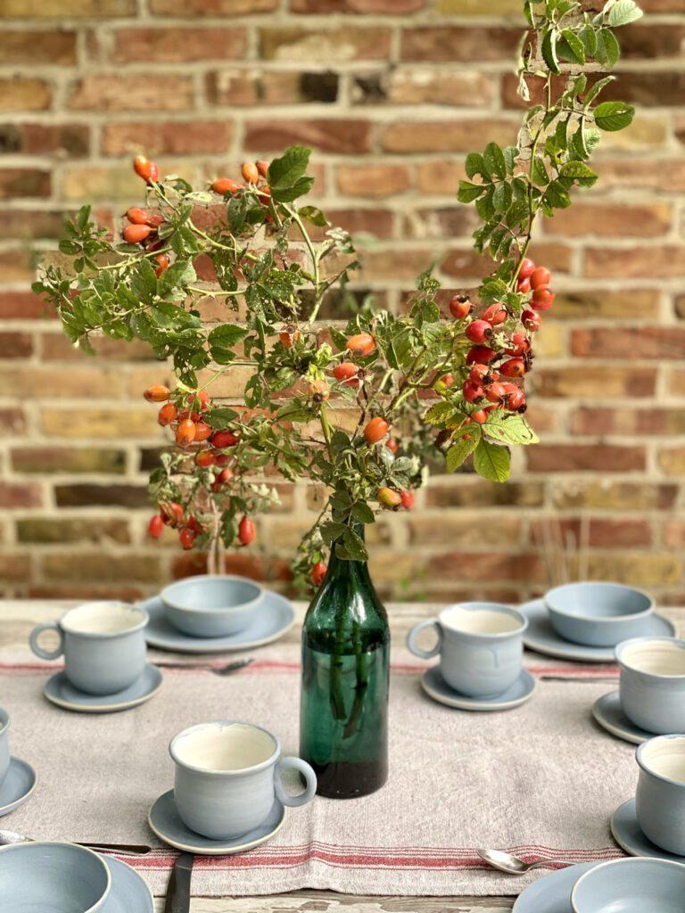 Hagebuttenzweige in Glas-Vase auf rustikalem Tisch vor Backsteinwand