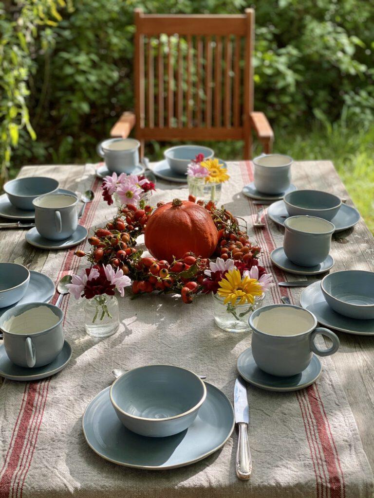 Hagebuttenkranz mit Kürbis in der Mitte auf rustikalem Tisch in grünem Garten