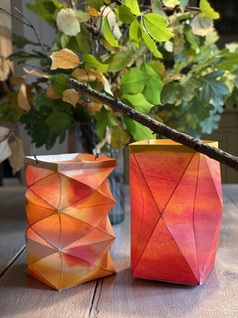 Zwei rötliche Waldorflaternen auf dem Holztisch, dahinter Herbstzweige in einer Vase