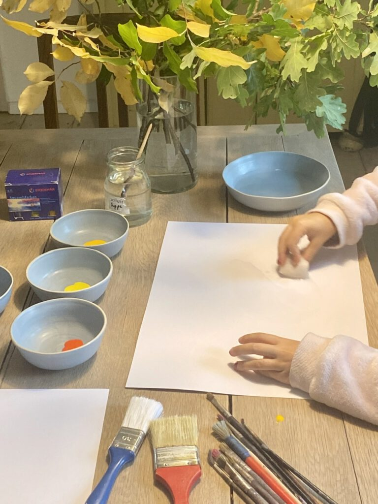 Kind nässt Papier mit Schwamm
