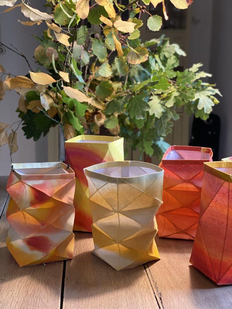 Mehrere Waldorflaternen auf dem Holztisch, dahinter Herbstzweige in einer Vase