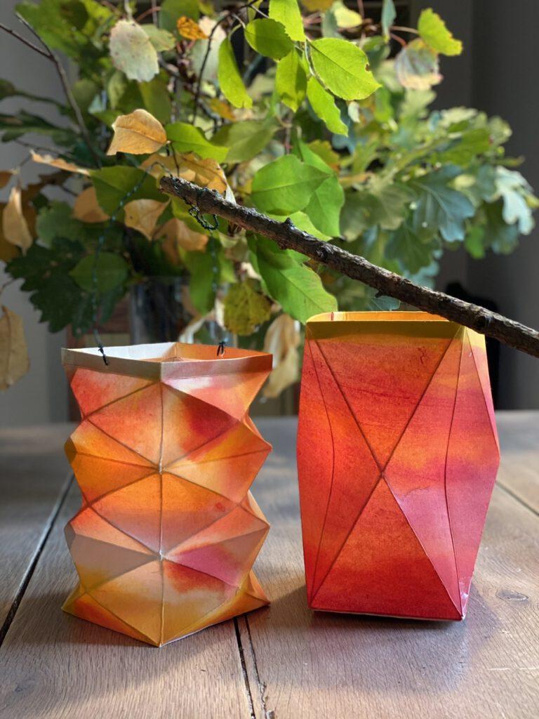 Zwei Waldorflaternen auf Holztisch vor Herbstzweigen