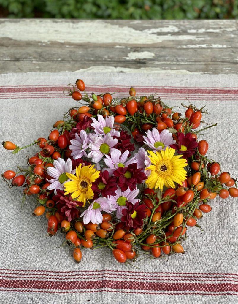 Hagebuttenkranz mit Blumen auf rustikalem Tisch von oben