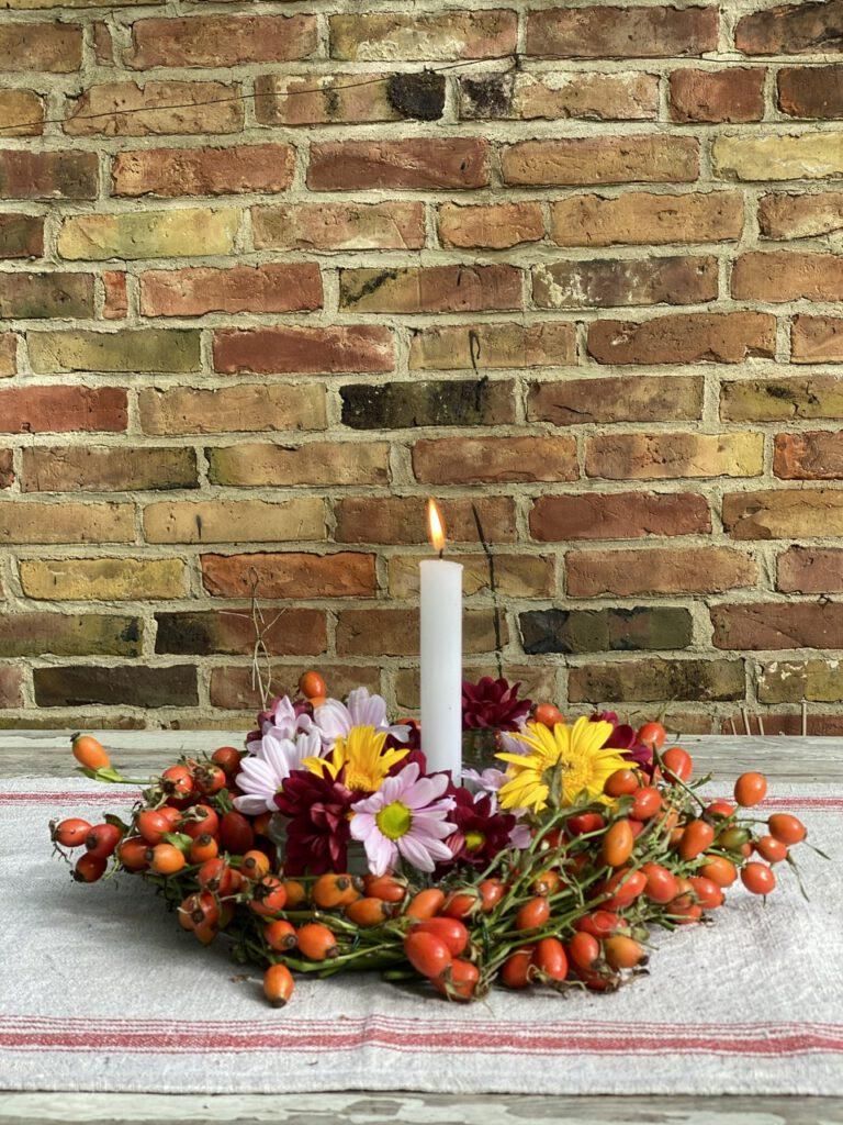 Hagebuttenkranz mit Blumen und Kerze auf rustikalem Tisch vor Backsteinwand