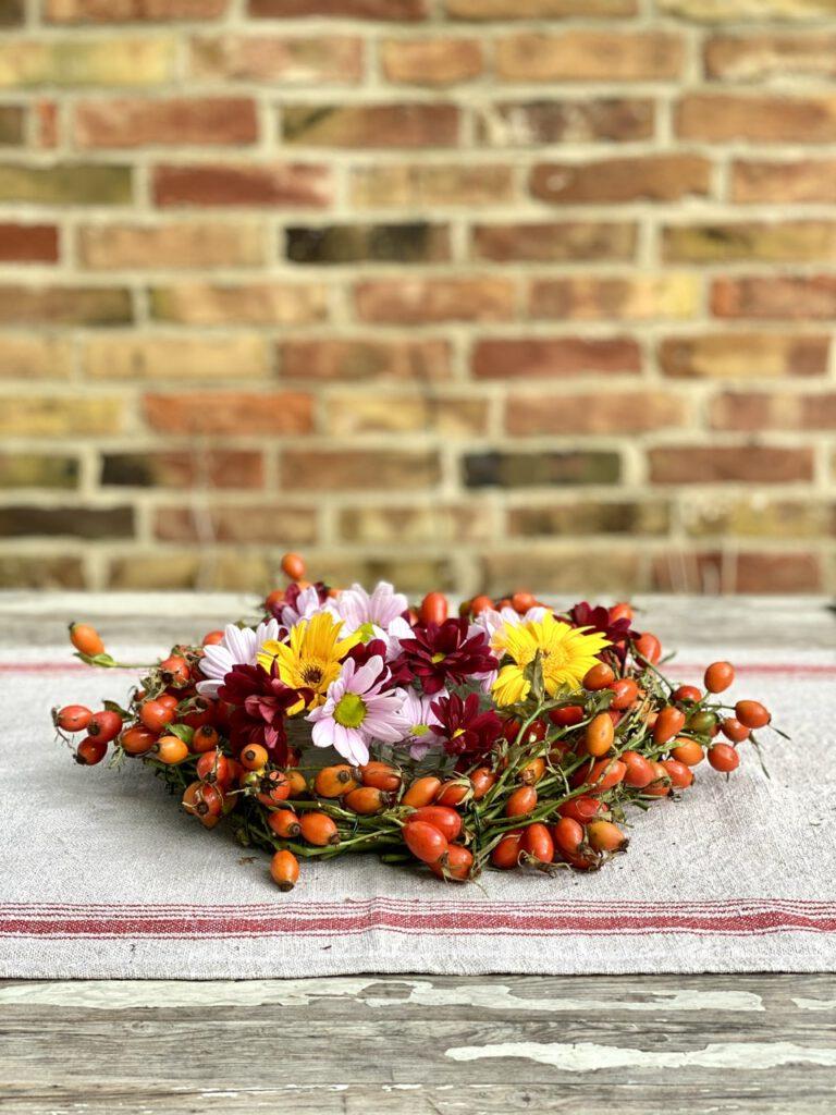 Hagebuttenkranz mit Blumen auf rustikalem Tisch vor Backsteinwand