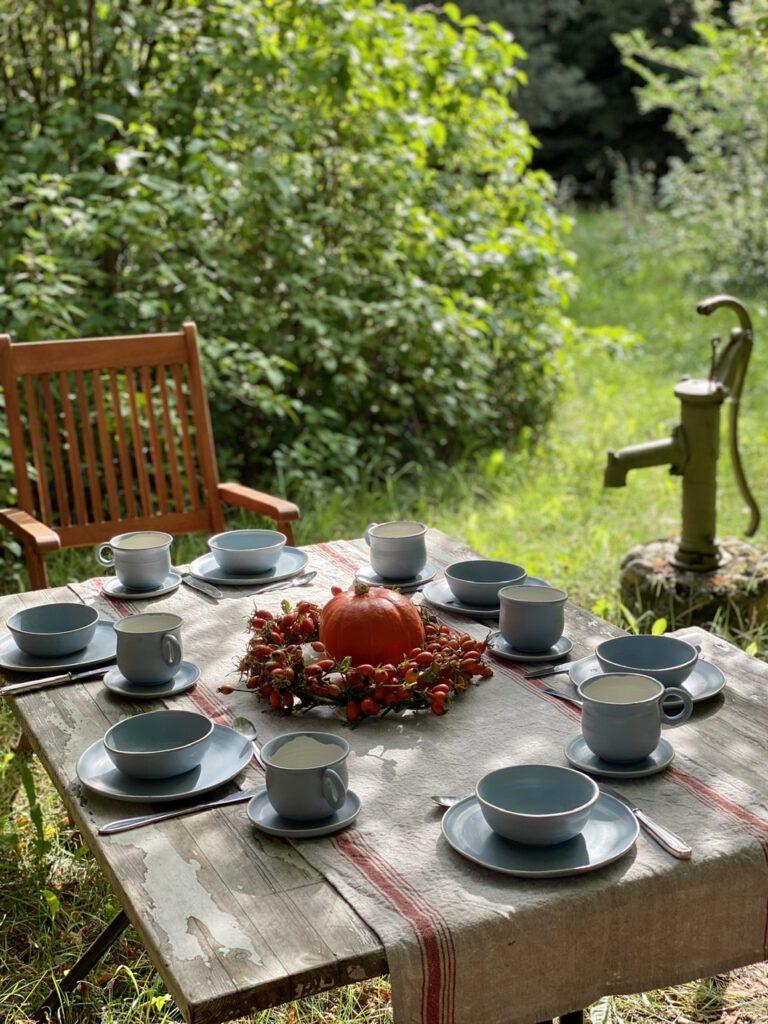 Hagebuttenkranz mit Kürbis in der Mitte auf rustikalem Tisch in grünem Garten, mit alter Wasserpumpe