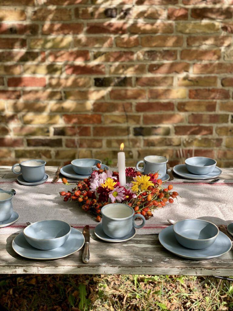 Hagebuttenkranz mit Blumen und Kerze auf gedecktem Tisch mit hellblauem Tongeschirr vor Backsteinwand