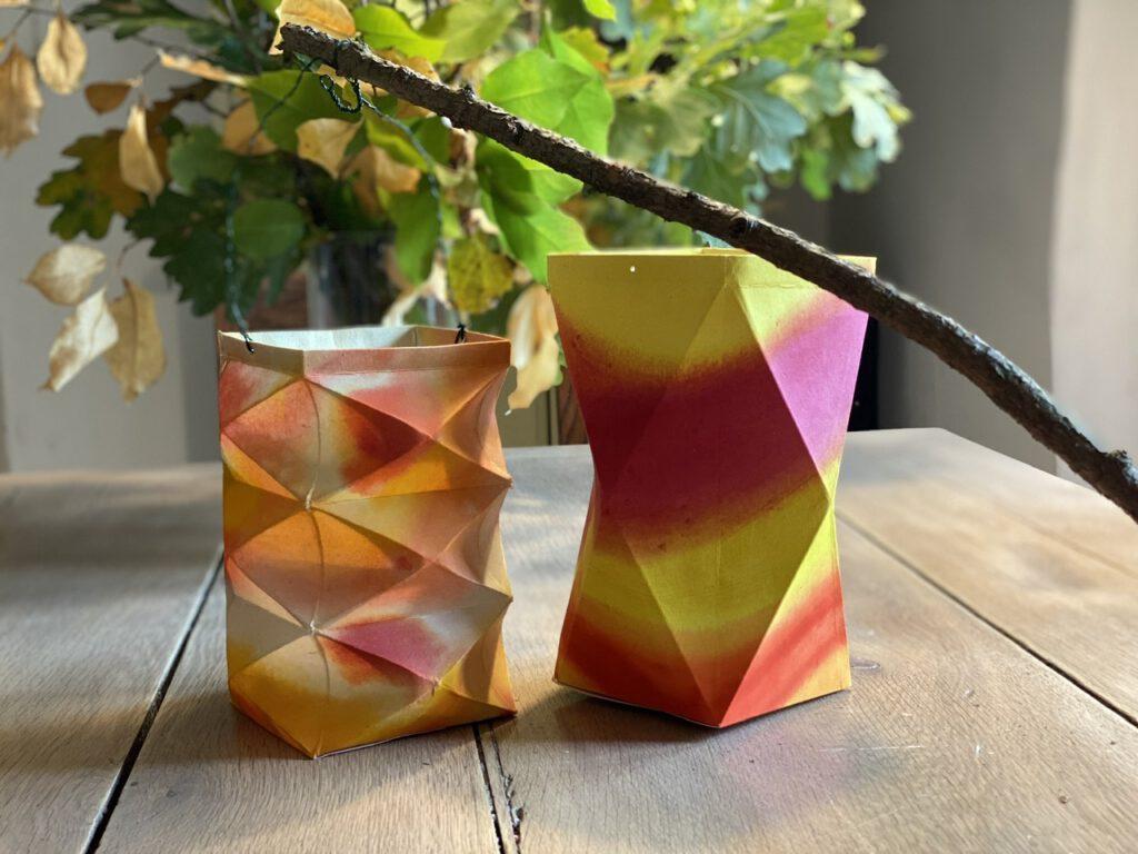 Zwei Waldorflaternen auf dem Holztisch, dahinter Herbstzweige in einer Vase