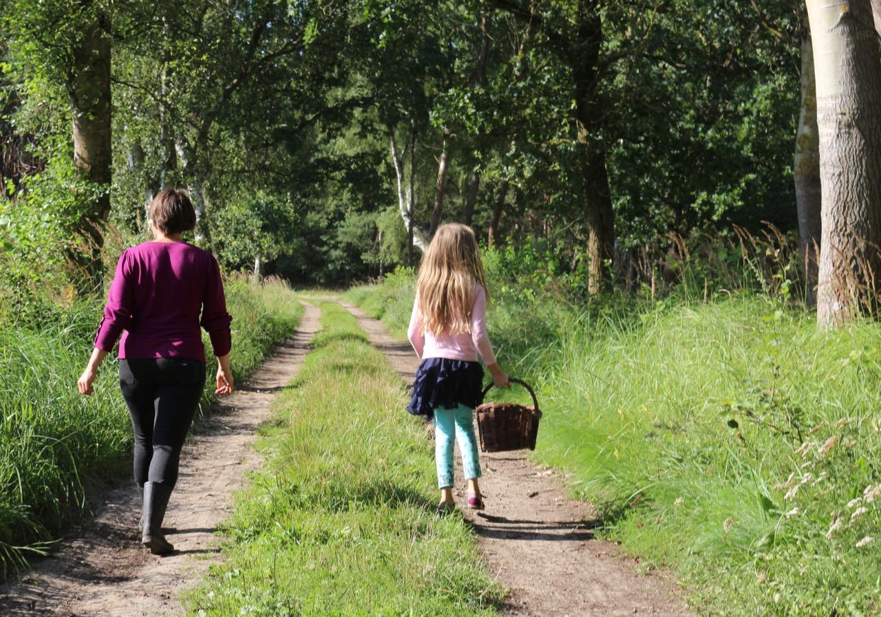 Maike und Tochter auf einem Waldweg, mit Korb in der Hand