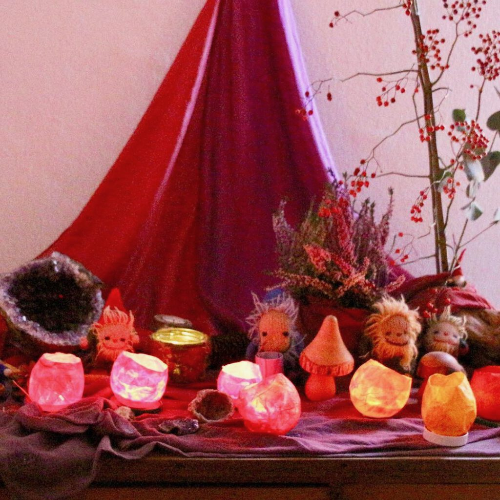 Jahreszeitentisch mit rotem Tuch, Wollzwergen nd vielen kleinen Laternen