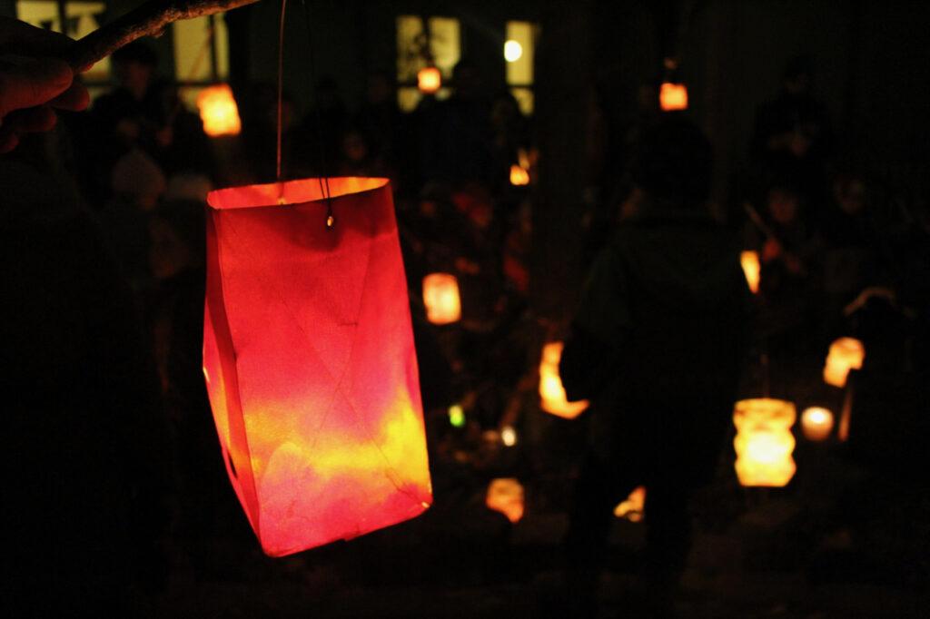 Leuchtende Waldorf-Laternen aim Dunkeln, eine groß im Vordergrund