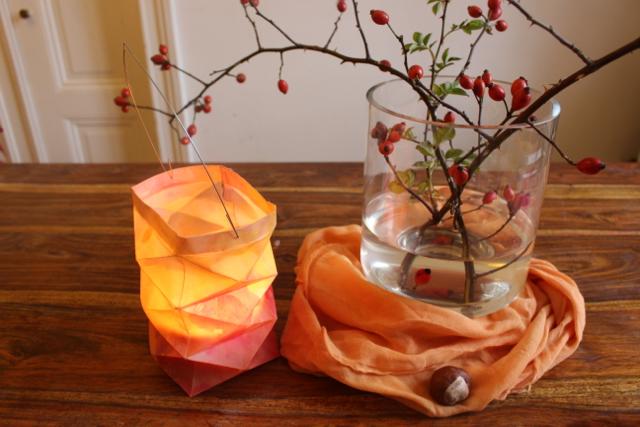Waldorf-Laterne auf einem Tisch von oben, mit Hagebuttenvase und Kastanien auf dem Tisch