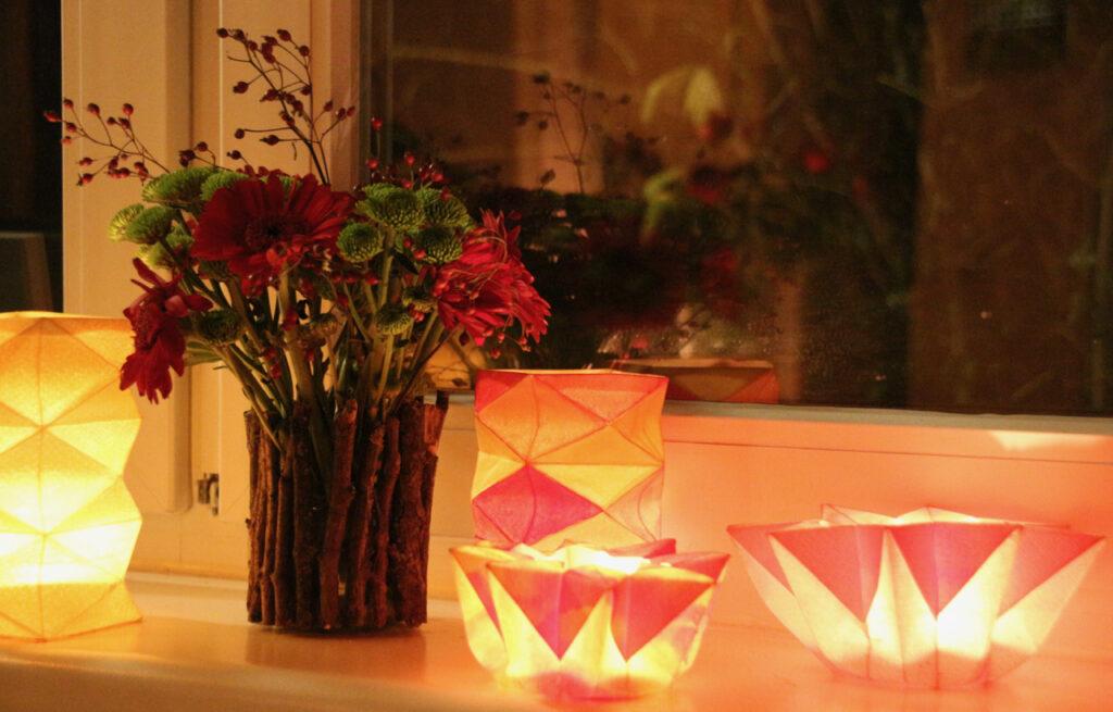 Waldorf-Laternen und Sternenlichter auf einer Fensterbank neben einer Vase mit Blumen