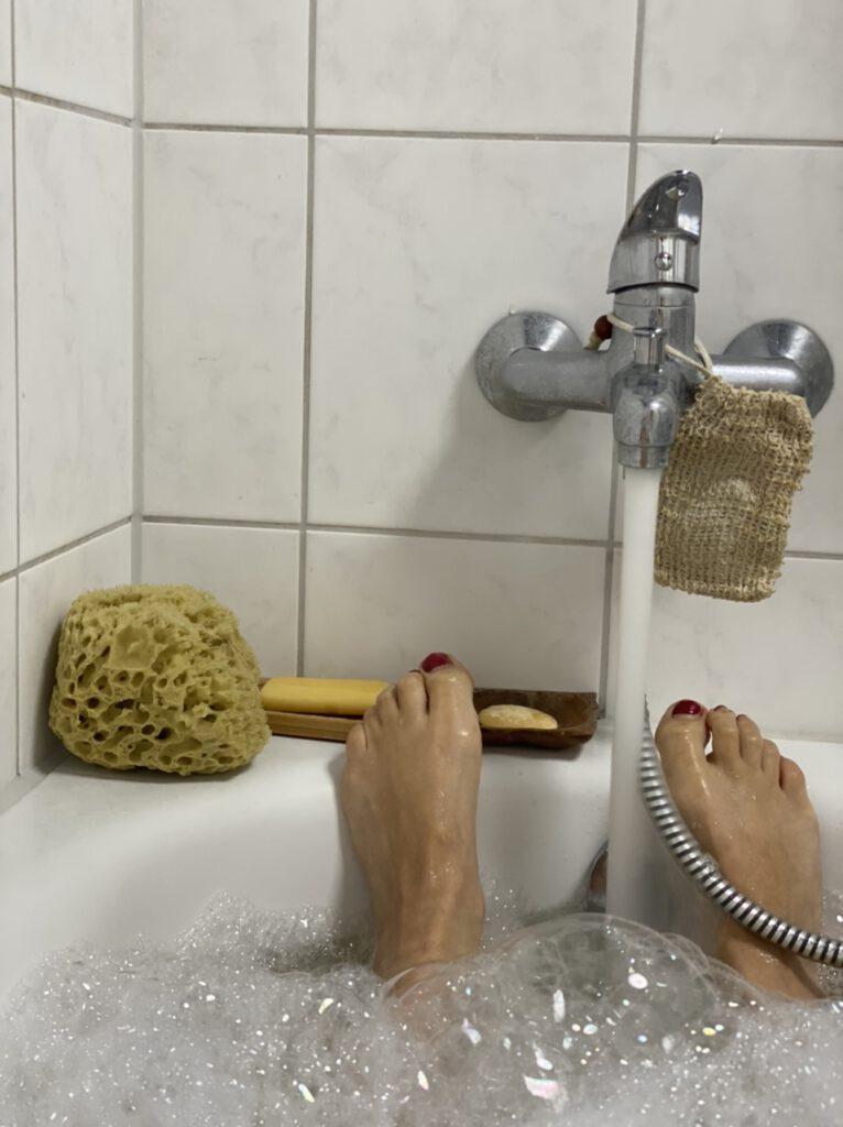 Körperliebe = Selbstfürsorge! - Bildbeschreibung: Füße im Bad und Wasserhahn, aus dem Wasser in die Wanne läuft, Naturschwamm auf dem Badewannenrand