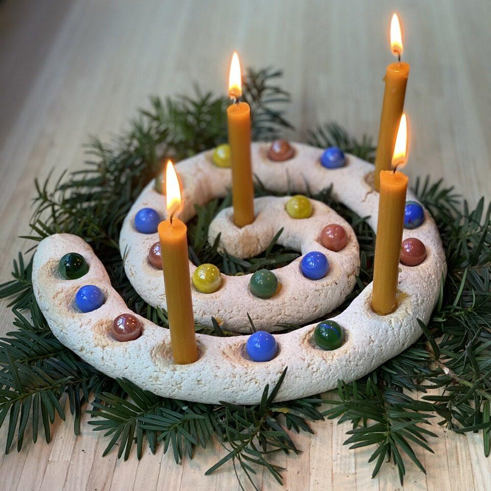 Adventsspirale mit 4 Kerzen, der Rest ist mit Murmeln ausgelegt.