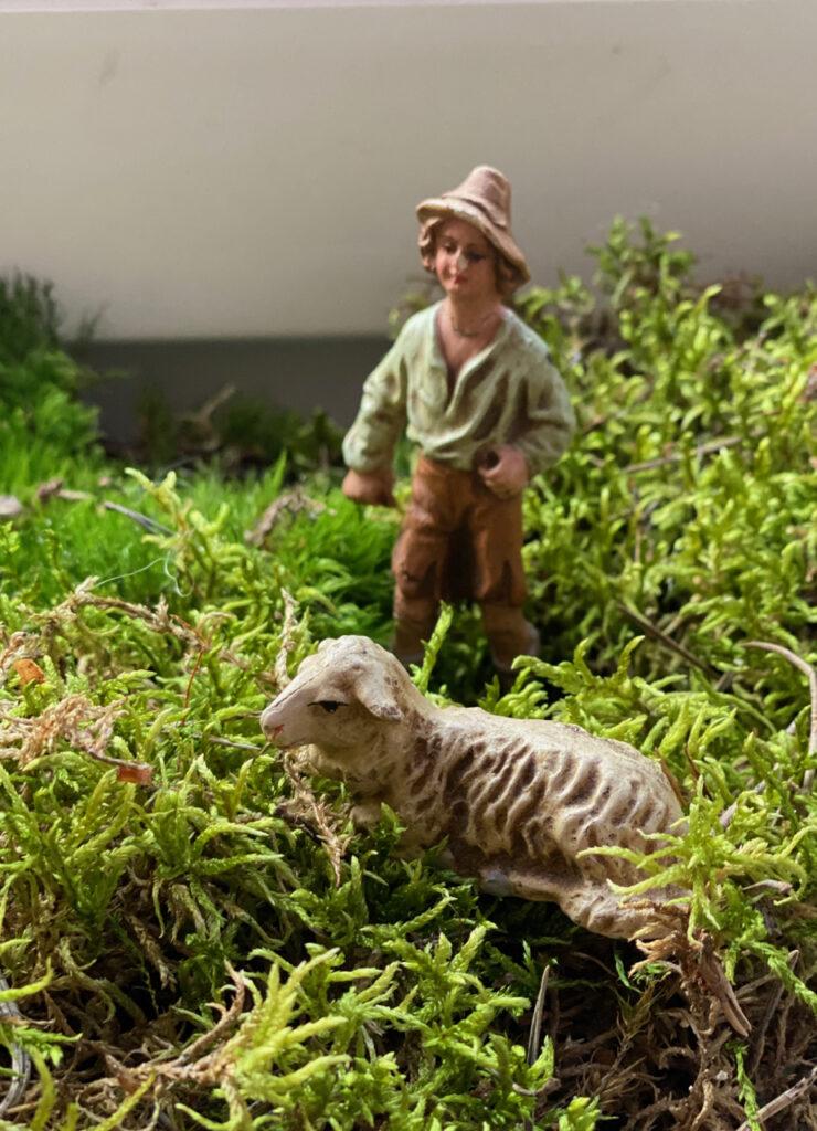 Alte Krippenfigur (Hirte) im Moos mit Schaf zu seinen Füßen